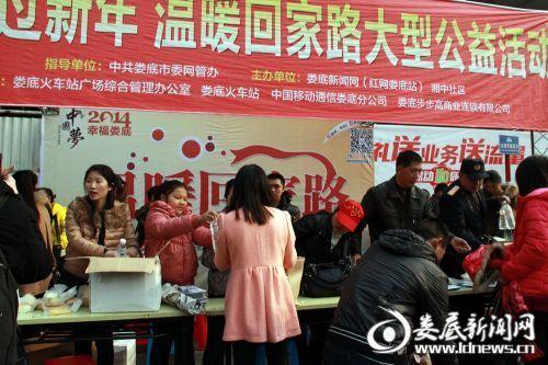 2014,温暖回家路活动现场,志愿者将爱心食物发放给返乡人员