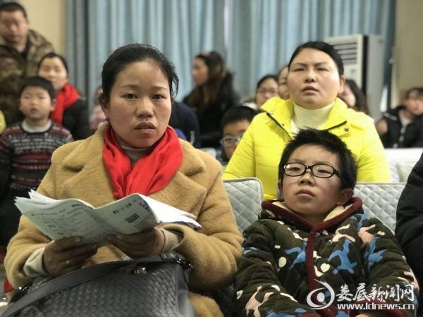 (9岁小朋友张伟铭和妈妈在讲座现场认真聆听斜弱视治疗知识讲座)