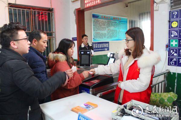 在娄底汽车站,工作人员正在为上车旅客验票。
