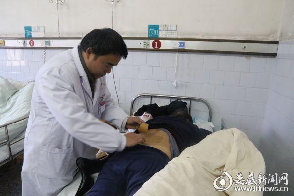 外二科副主任医师黄伟雄为朱大爷正在做理疗