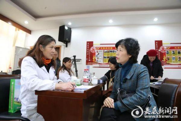 医务人员为该局职工解答体检报告、测量血压等