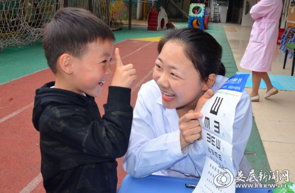 娄底爱尔眼科医院的医务人员耐心指导孩子辨别视力表