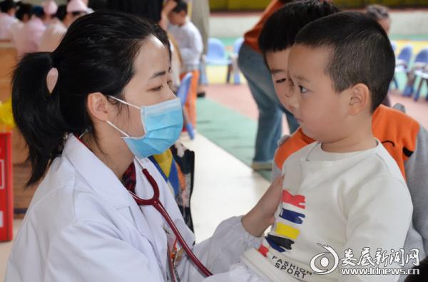娄底市妇幼保健院儿科医生李莉在体检现场为孩子检查身体