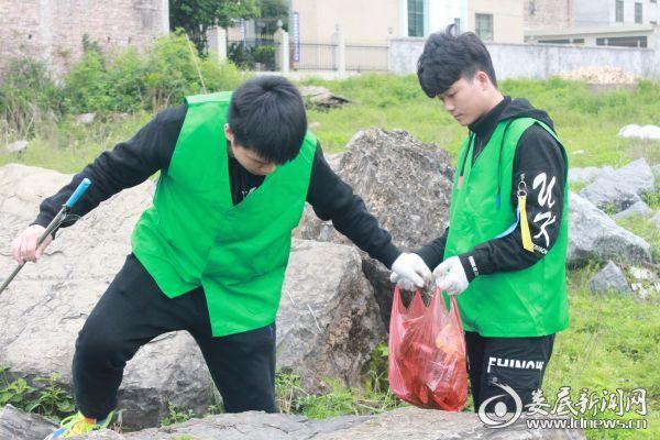 (志愿者穿着绿马甲,拿着工具,戴上手套,为保护绿水青山,奉献出青春的力量)