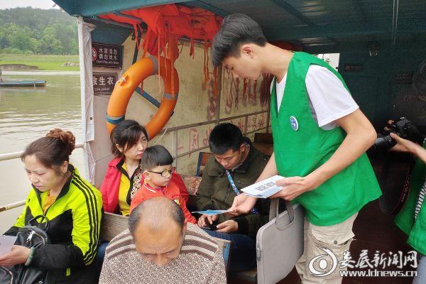 志愿者梅山龙宫登船口给过往的游客分发宣传手册