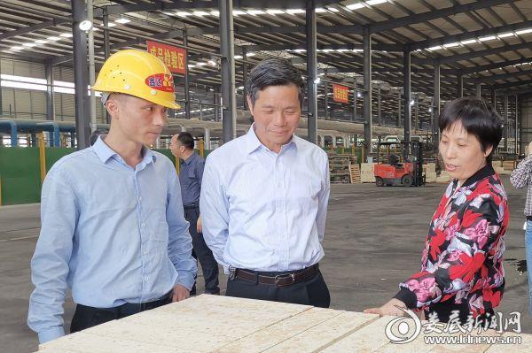 鑫达高硅耐火材料厂生产车间内,企业负责人向肖有胜汇报企业相关情况