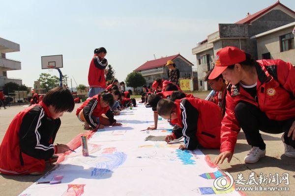 (洁白的画布在操场上铺展开来,学校的孩子们汇聚在一起,或蹲、或趴,或席地而坐,大家奇思妙想,用形式多样的绘画材料,将心中的梦想与生活的美好一起融入到画卷中来)