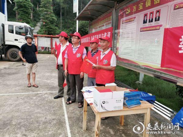 (演出前,志愿者向来观看晚会的村民发放宣传册 )
