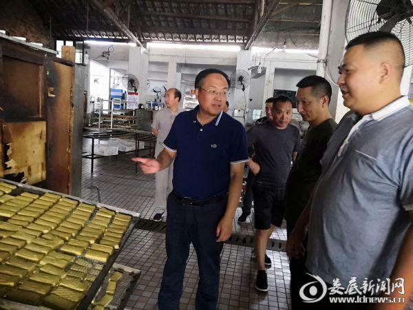 (杨韶红(左一)察看产品生产流程)