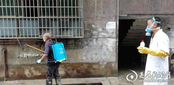 (涟溪桥社区老耐火厂家属区工作人员在对受淹房屋进行消毒杀菌)