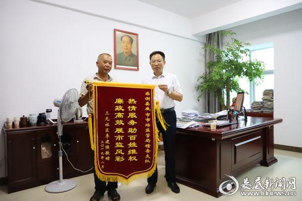 娄底市市场监管局邓志洪局长(右)收到百姓送来的锦旗