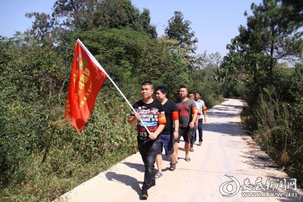 """""""群防群治守护家园""""志愿服务队的队员进村巡查油茶林 (1)"""