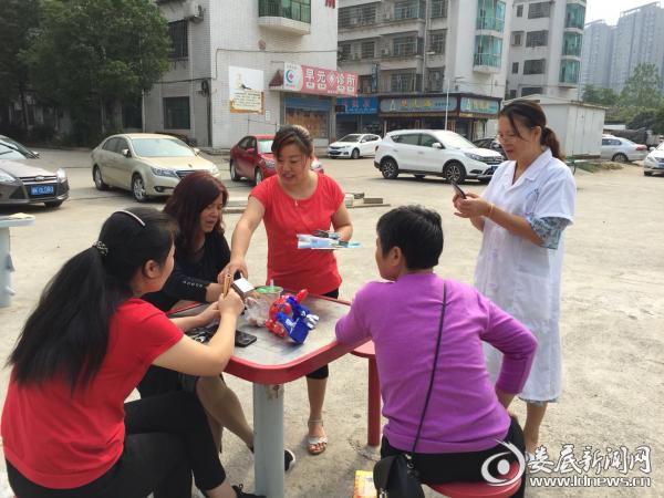 (工作人员向居民发放免费避孕药具及宣传资料)
