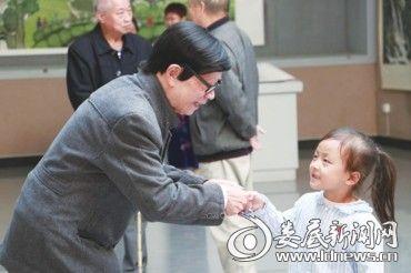 """李仕奇老人握着一位小女孩的手说:""""谢谢你,来看我的画!"""""""