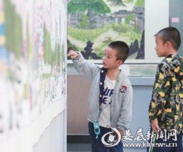 """小男孩指着画上的某处,告诉他的同伴:""""我家住在这里。"""""""