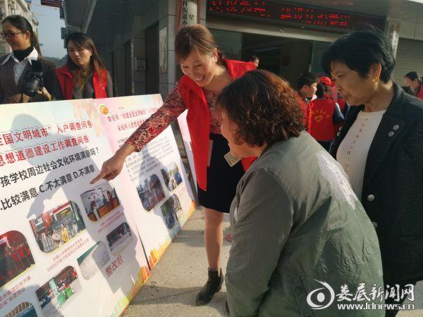 (教师志愿者们正在为南垅社区居民讲解展板上的创文知识)