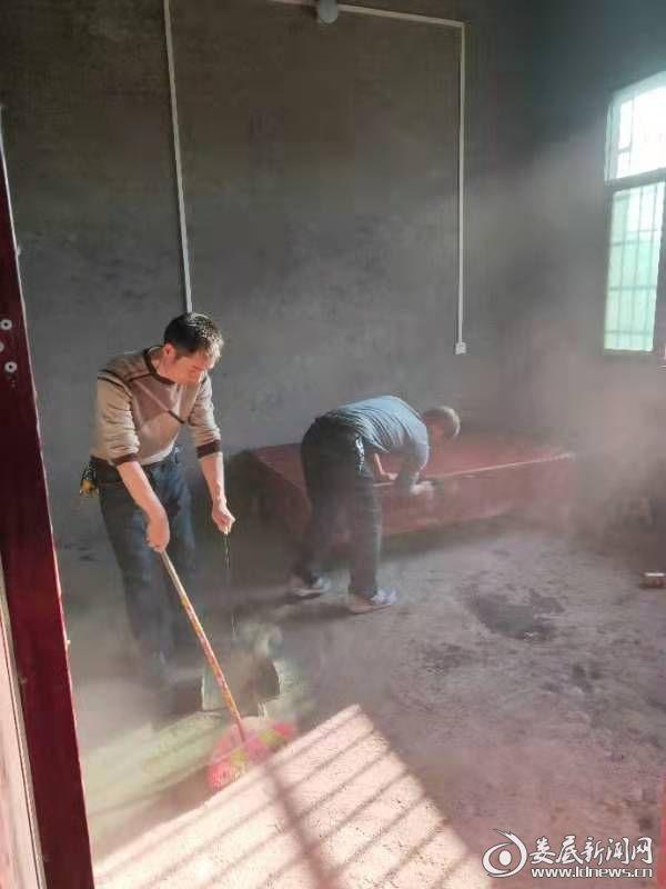 图2:帮扶责任人给贫困户家中清洁卫生