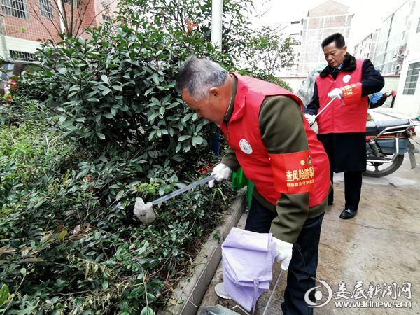 志愿服务队队员在绿化带清理垃圾