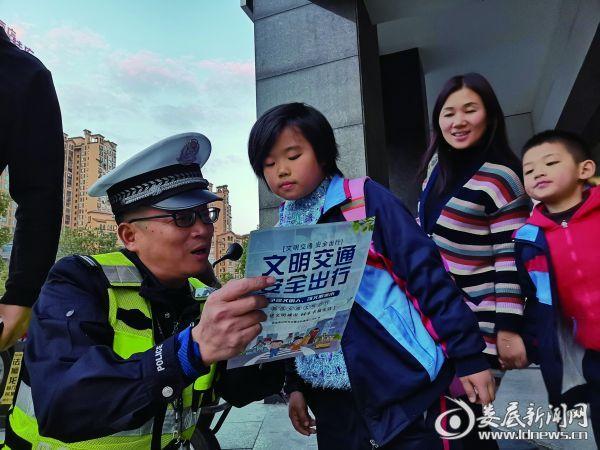 交警在街头为一小学生讲解安全知识,路过群众驻足观望