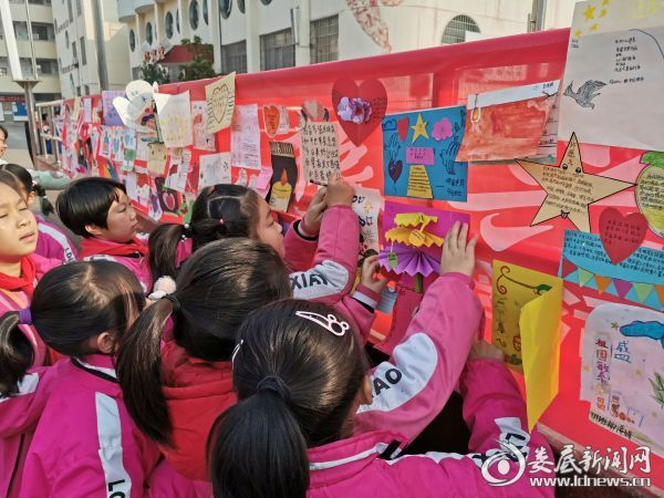 """(孩子们将自己的""""红领巾许愿和平卡""""贴在红领巾和平许愿墙上)"""
