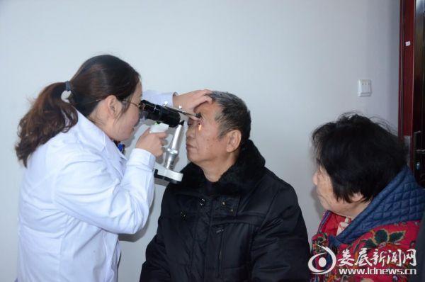 (眼科医生为居民们进行眼健康检查)