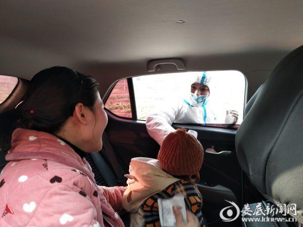 在320国道界峰段卫生检疫站,过往车辆上的群众正积极配合工作人员的体温检测。