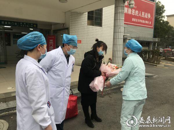 (仪式上,朱女士向医务人员深深地鞠躬并献上鲜花,衷心感谢他们在住院期间的精心治疗,感谢他们冒着被感染的生命危险挽救了她的生命)