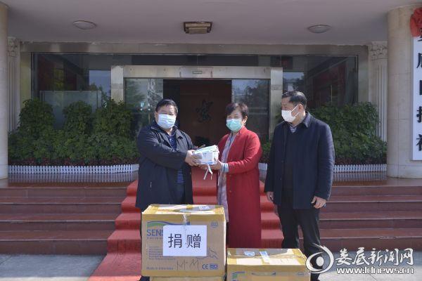 娄底市华蓝贸易有限公司董事长彭丽华(中)向娄底日报社捐赠一次性医用口罩