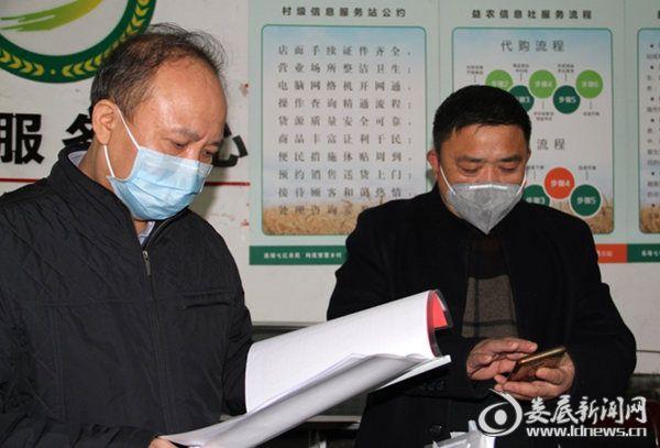 毛健刚(左)查看桥头河镇桂花村便民服务中心疫情摸排情况登记表