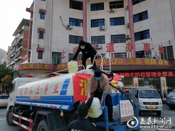 (上渡街道防控人员正在卸载消毒液)