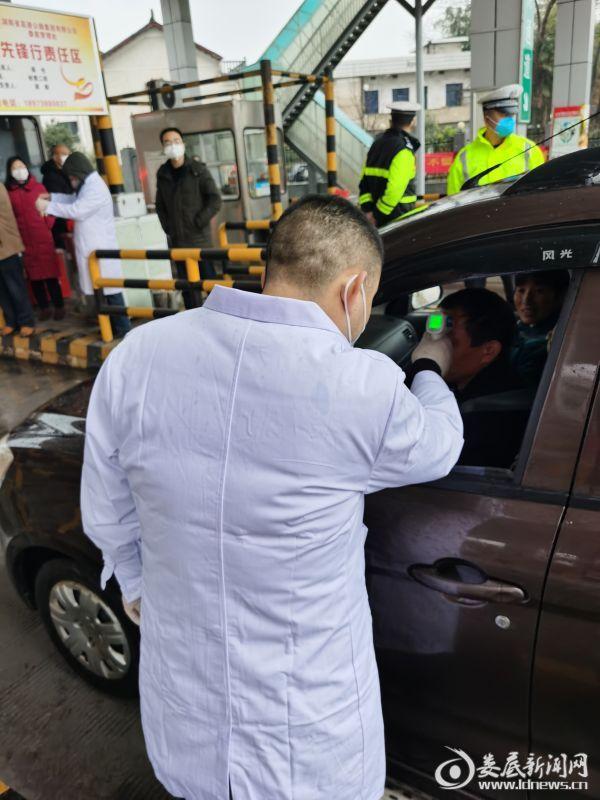 金竹山镇卫生院院长谢湘峰在高速路口为返乡人员测量体温(3)