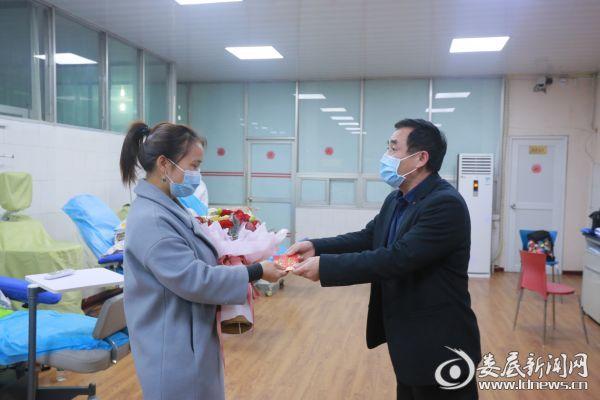 娄底市中心医院党委委员、副院长陈福如(右)为朱女士(左)送上鲜花和慰问金