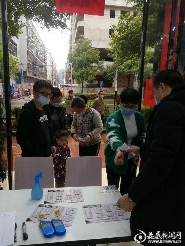 1百年吉祥饺子馆工作人员为顾客测量体温