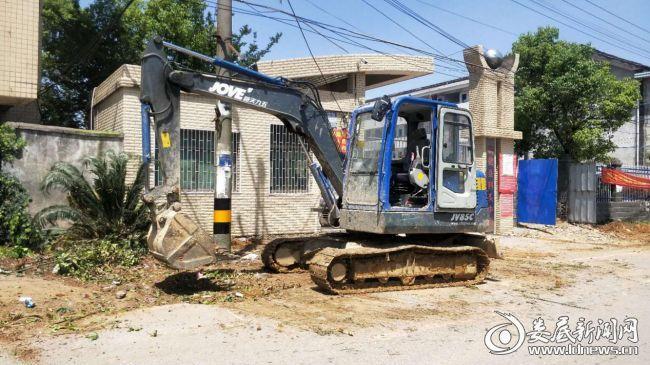 (图为学校传达室前被非法侵占的围栏和种植的树木被清除场景)
