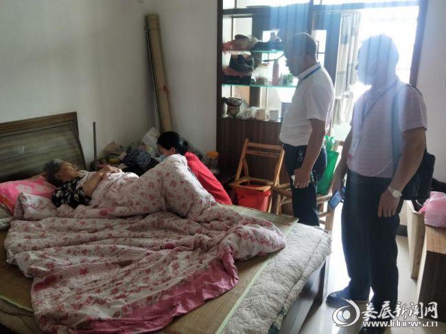 工作人员入户为行动不便的老人进行检查和问诊