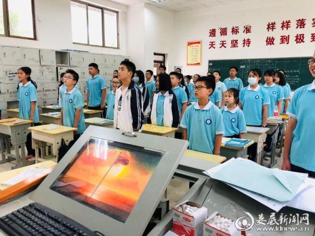 (同学们在教室里参加网上升国旗仪式)