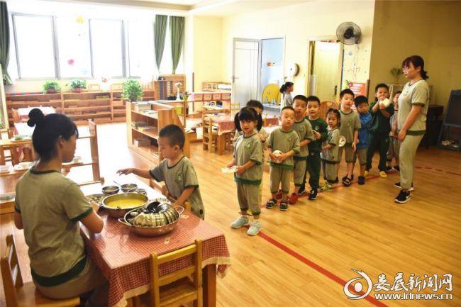 孩子在老师的引导下有秩序地排队吃早餐