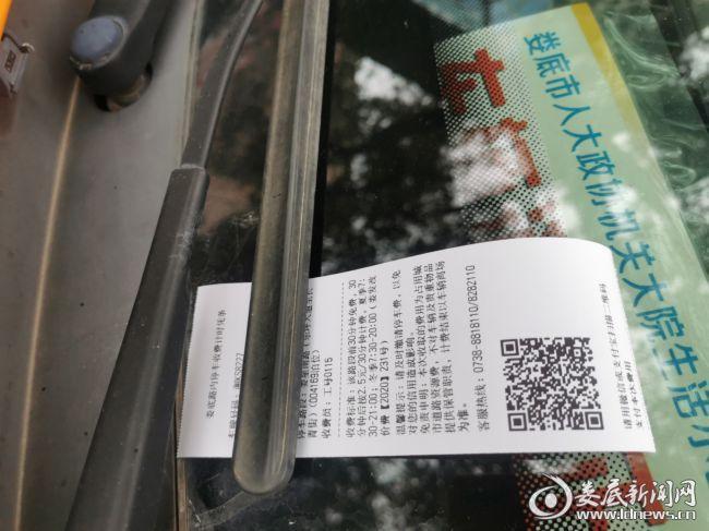 (图为收费员放于泊车车辆指定位置上的缴费二维码小票)