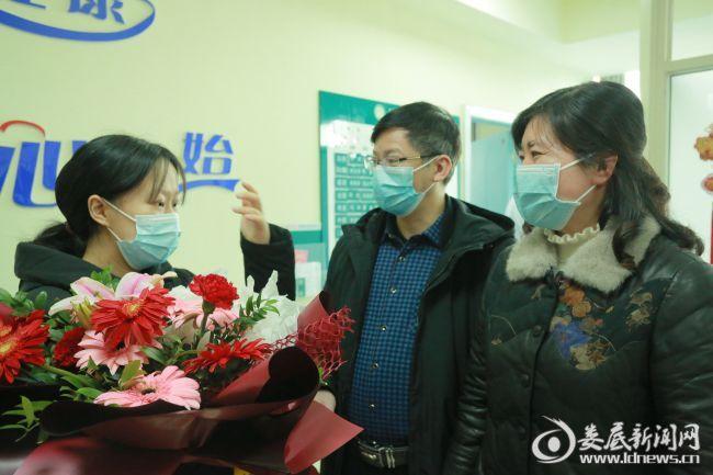 出院时,英英流下激动的泪水,该院党委副书记、纪委书记姜海燕(右一)为英英送上鲜花,祝贺她康复