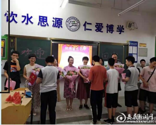 (图为李红育老师[第二排左四]接受留守儿童感恩赠送的鲜花)