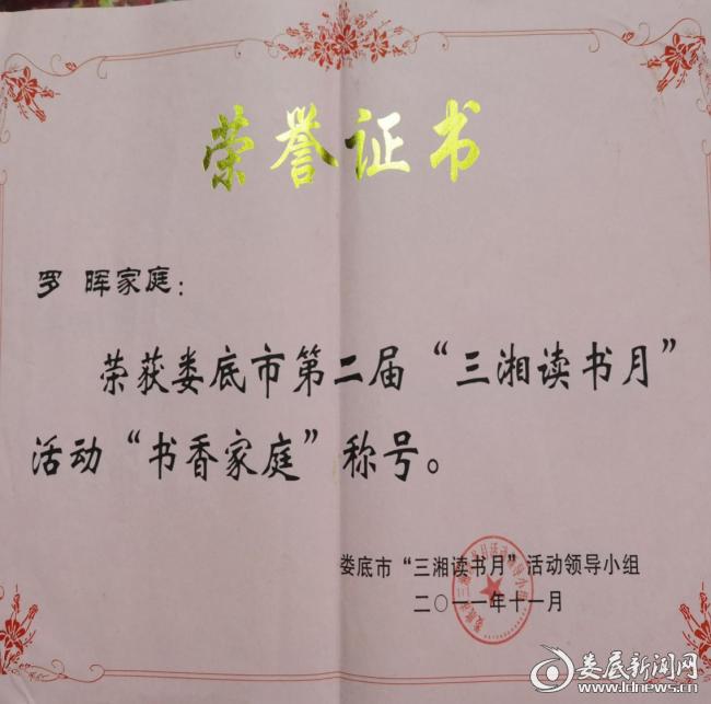 """(图为罗晖、李红育夫妇一家被评为""""娄底市书香家庭""""荣誉证书)"""