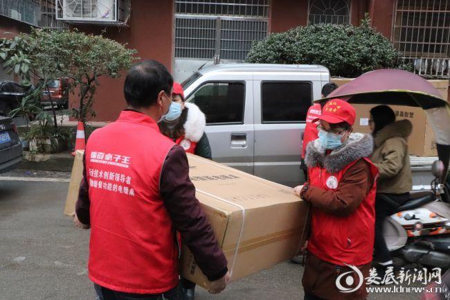 (志愿者和送货员一起搬运电暖桌)