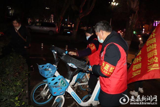 (见到共享单车未在规划区域内,志愿者一同将单车整齐摆放好)