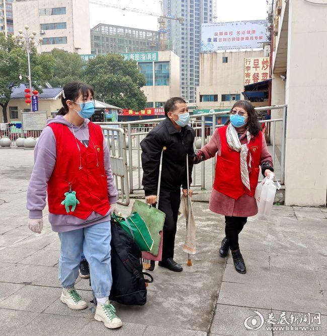志愿者帮助行动不便的旅客提行李