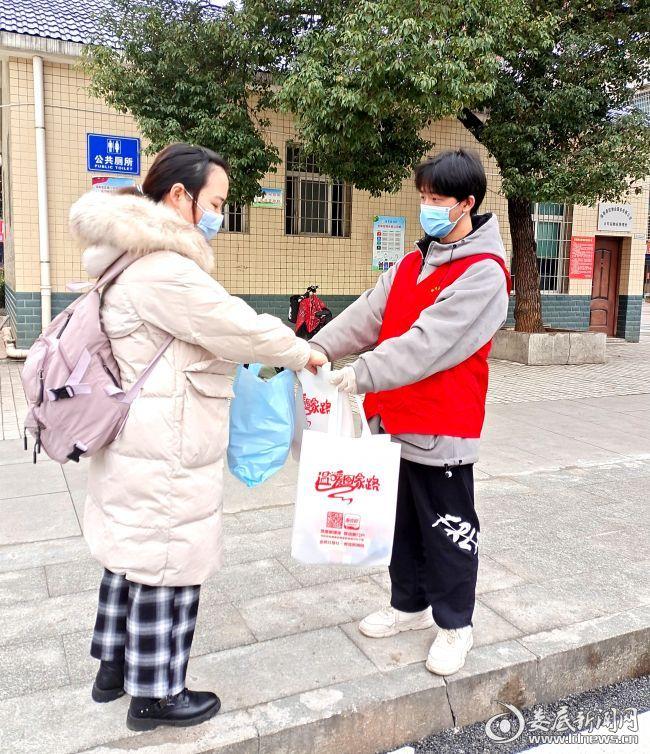 """志愿者将装有饼干、矿泉水、便民服务手册的""""温暖包""""送到返乡人员手中"""