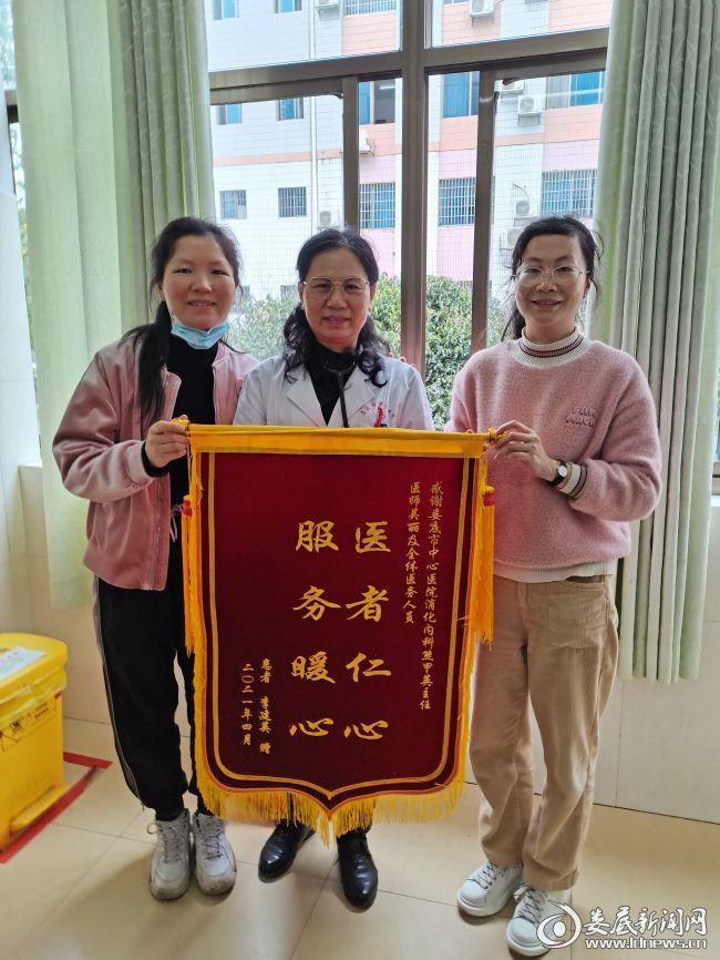 李阿姨的家属将锦旗送到熊甲英主任(中)手上