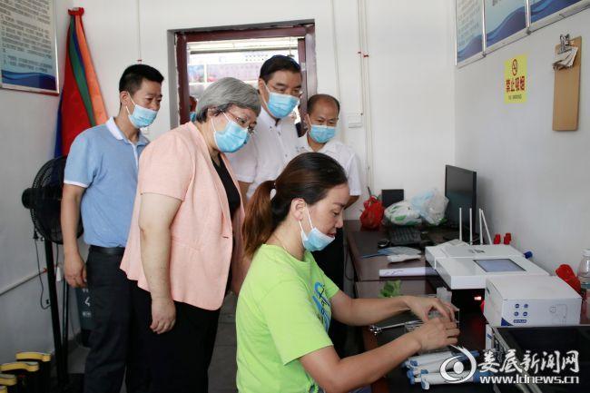 (在农贸市场农产品质量检测室,石艳萍详细了解农产品抽查检测情况)