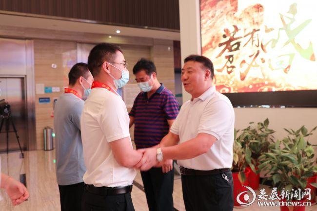 """(市委副秘书长刘小辉为退役军人代表佩戴""""光荣退役、再立新功""""绶带)"""